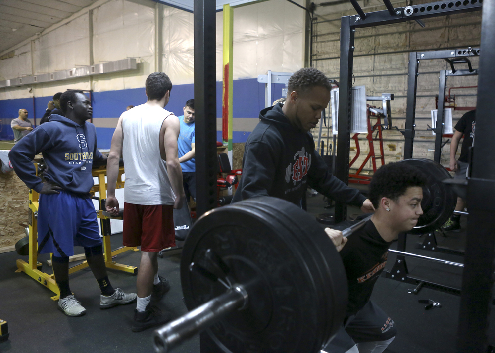"""Steven Whitehead spots Jared Gray, Kennewick High School junior, as he lifts weights during a early morning training session with high school athletes at Elite Ambitions Training in Kennewick. Whitehead, founder and owner of E.A.T., says he isn't a typical trainer who says """"good job,"""" but instead pushes those he works with."""