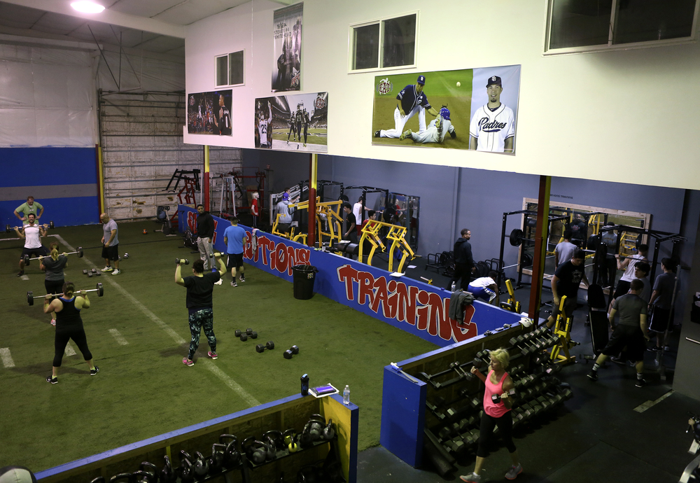 A photo of Steven Whitehead from his Tri-Cities Fever days hangs on the wall with other professional athletes during early morning fitness classes and weight training at Elite Ambitions Training in Kennewick. . Whitehead is the founder and owner of Elite Ambitions Training on South Washington Street.