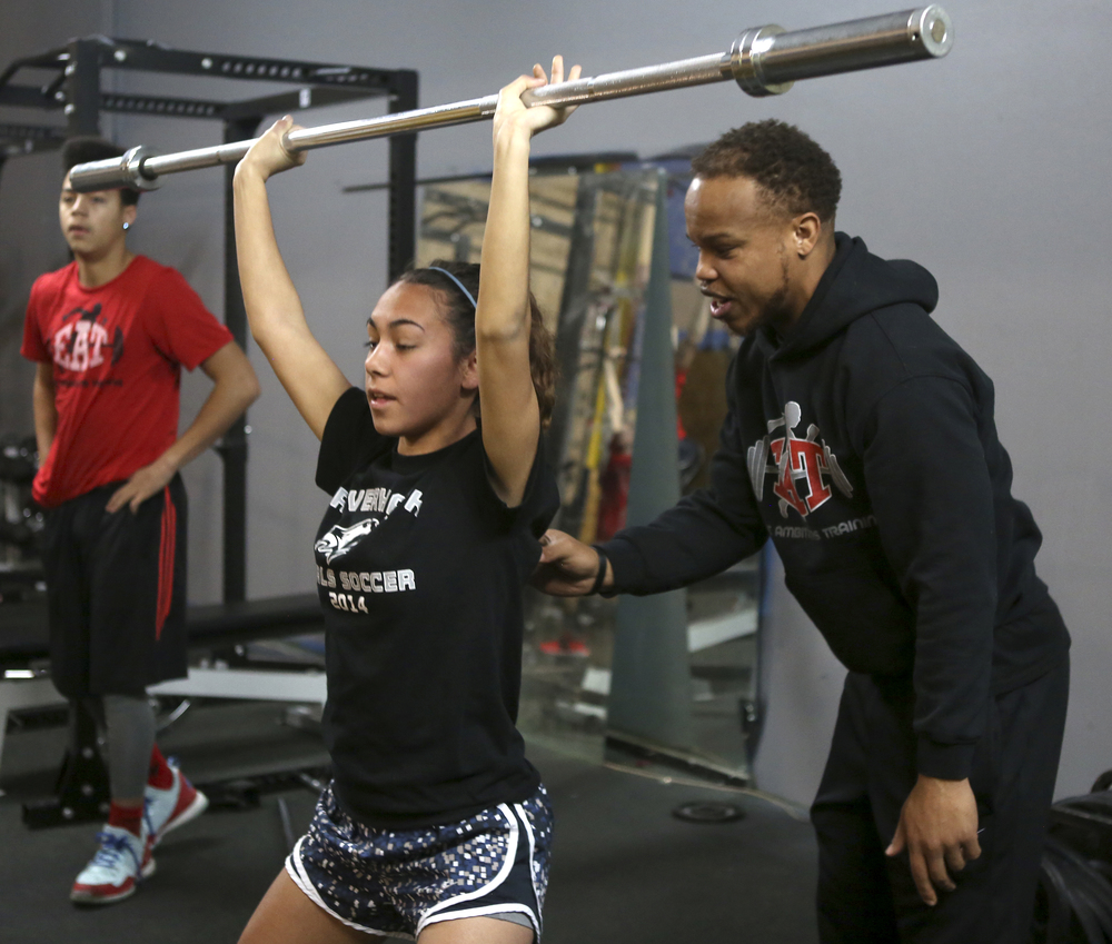 Steven Whitehead helps Justice Aragon, a senior at Chiawana High School, with her form while doing a squat during a early morning training session with high school athletes at Elite Ambitions Training in Kennewick. Whitehead, founder and owner of E.A.T., runs multiple training classes for high school athletes