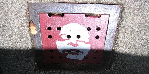 face on red sidewalk grate