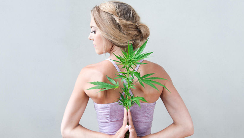 Rachael Carlevale, founder of Ganjasana, with cannabis plant. Photo by Tracey Eller (ellerimages.com), courtesy @CosmicSister