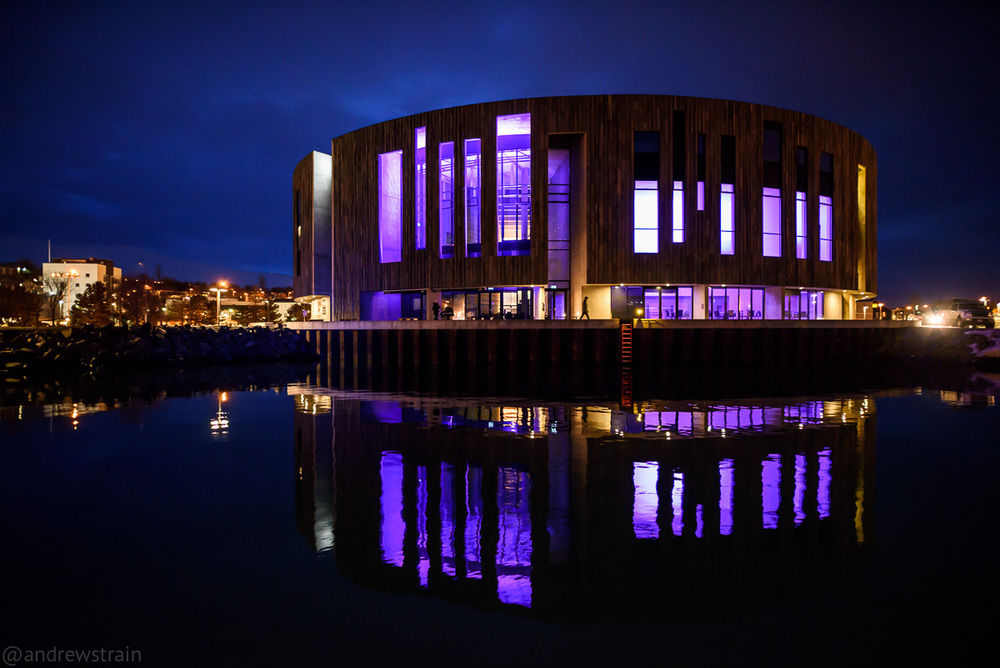 Nikon D810 + Sigma 20mm f/1.4 Art @ f/1.4 | 1/20 sec | ISO 3200 The maximum aperture of f/1.4 allowed me to gather enough light to shoot this image of the Hof Cultural and Conference Center, handheld from a sailboat in the harbour of Akureyri, Iceland.