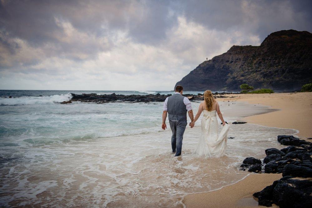 newly married couple walking on a beach in Oahu
