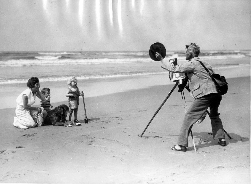 Een strandfotograaf aan het werk op het strand. Met zijn camera op een statief fotografeert hij een moeder met twee kinderen en een hond voor de zee. Ca. 1930. Nederland Plaats onbekend.
