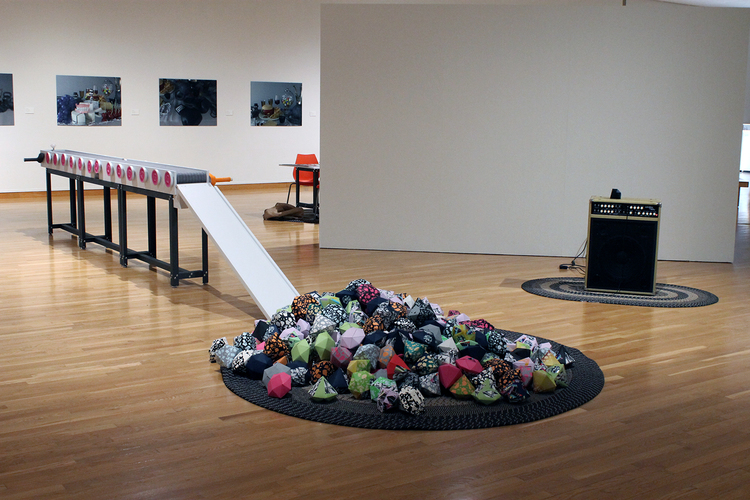 "Installation view,   LVL-UP!   2016.  17 ft. wooden conveyor belt, quilted belt, gem pile.  Sound component (amplifier on right) played a ""level up"" sound as gems were added to the pile."