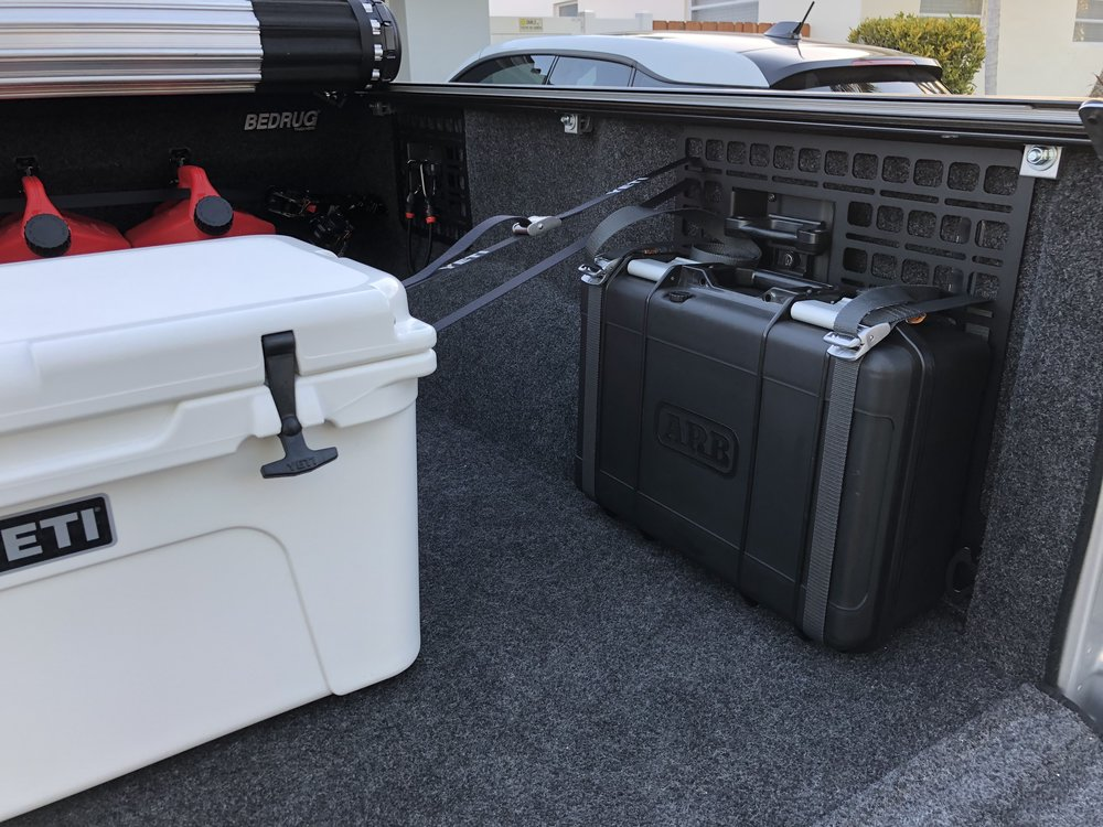 A BuiltRight customer keeping his cooler and ARB compressor in place using the Bedside Rack system in a 2018 Ford Raptor.