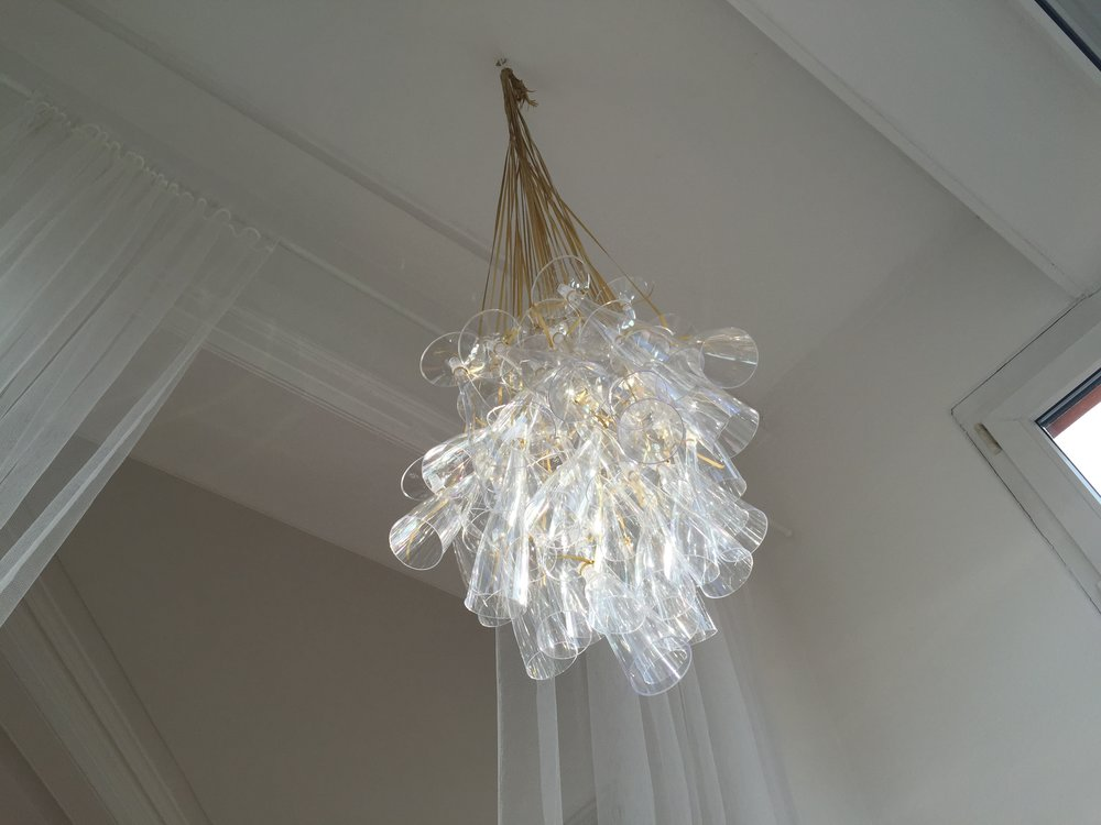 Chandelier hanging from ceiling from a simple metal hook.