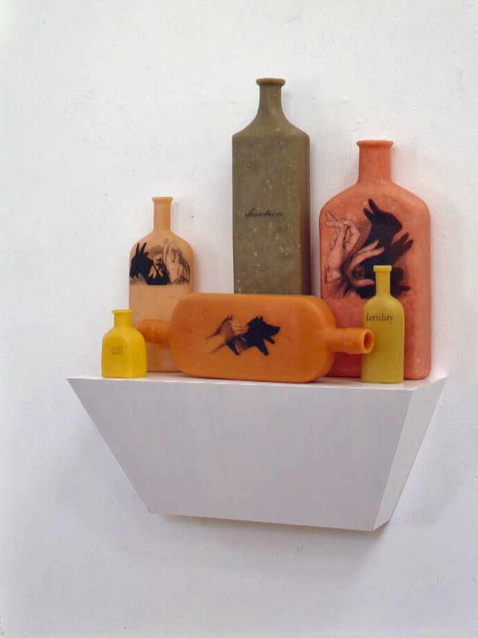 Whispering in the shadows,  1998: 22 x 18 x 6 inches, wax, pigment, wood.  The three bottles read lust, devotion, fertility; on their backs, a second set of words read obstinacy, infidelity, timidity. Each pair of words is associated with the animal represented nearby--respectively, a goat, a dog, and a rabbit.