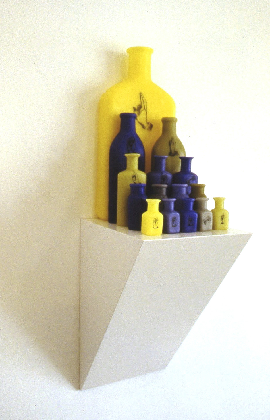 Reading is Seeing,  1999: Wax, wood, applied text/image; 25 x 9 x 7 inches. The sign language hands spell out the title of the piece.