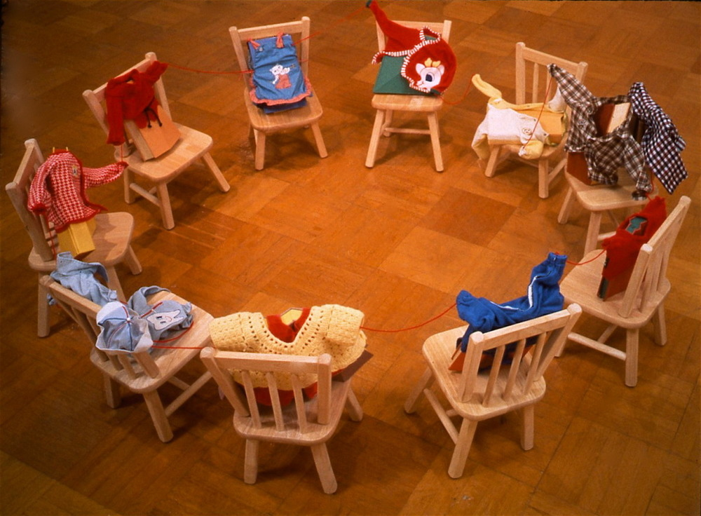 Kinderschule,  1992: books, oil paint, altered chairs, used children's clothing, red yarn.  Approximately 10 feet in diameter