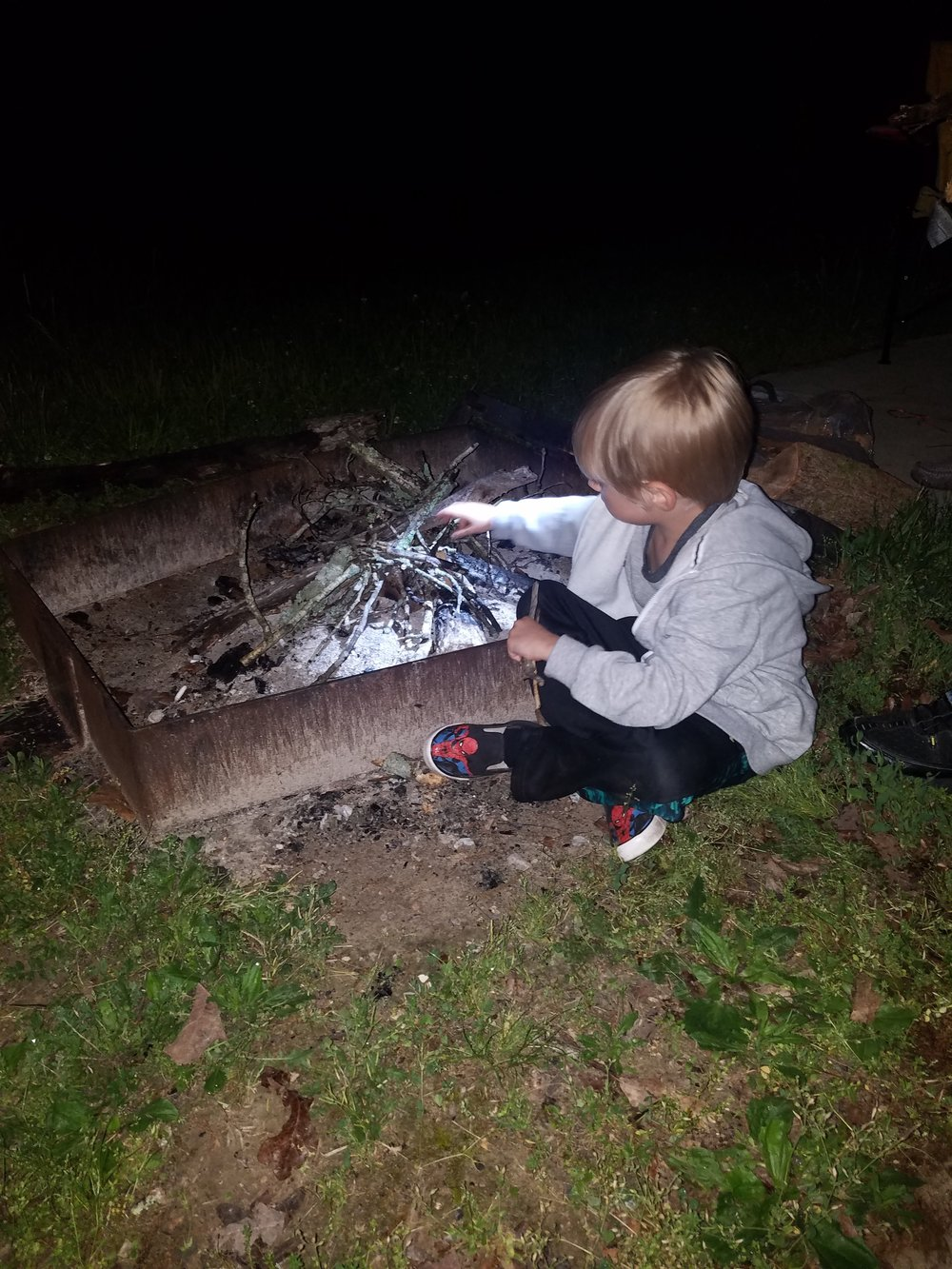 My nephew building up the brush for a fire...never too young to learn...