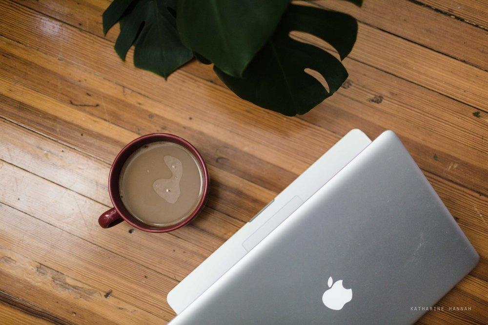 Coffee and a MacBook on hardwood floors