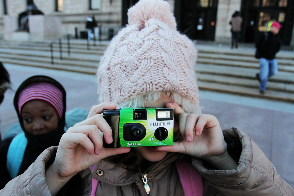 One of the female students taking pictures with her camera.