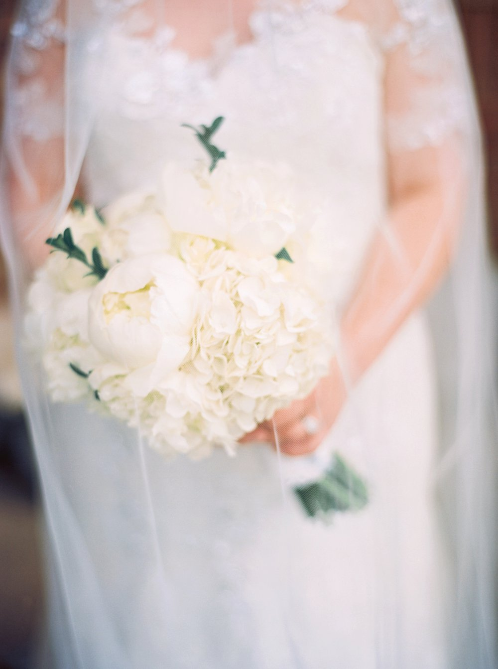 Love this shot of the veil covering the floral bouquet.