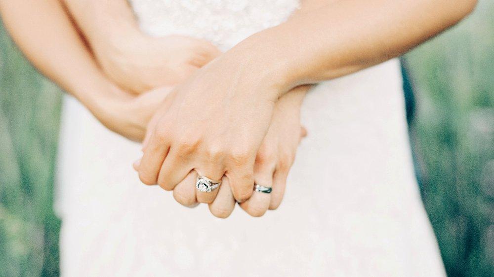 Newly married, hands clasped together. Captured with a Contax 645 camera on Kodak film.
