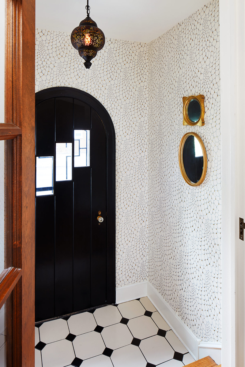 Claire revitalized the gorgeous arched-door and the original black and white tiles by incorporating some gorgeous wallpaper by Relativity Textiles into their front entryway.