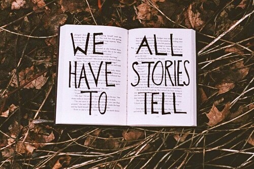 "[Photo of an open book with the words ""WE ALL HAVE STORIES TO TELL"" written on top of the text on the white pages. The open book lies on top of fallen brown leaves and sticks.]"