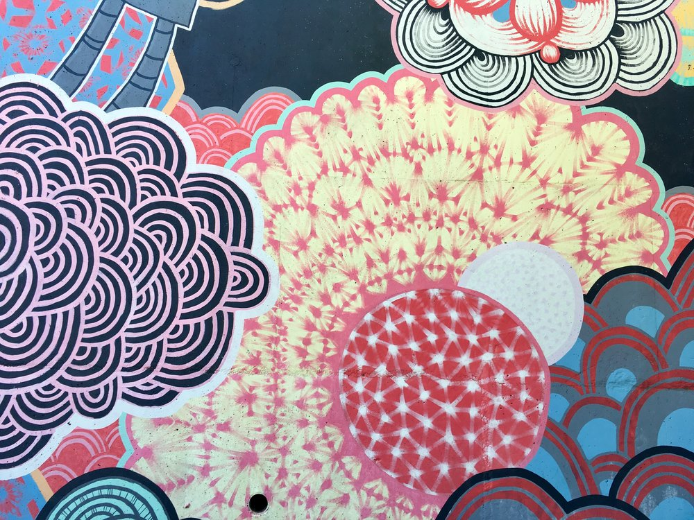 [Photo of a mural in Atlanta filled with abstract flower-like shapes in pinks, reds, blues, blacks, whites and mint green. Photo by MM.]