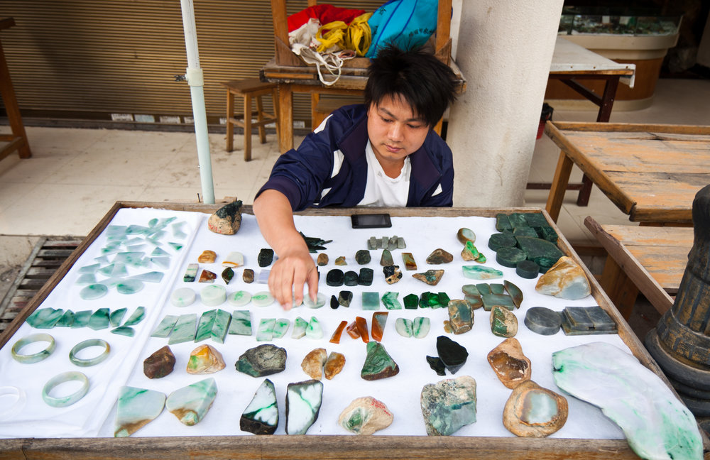 A trader sells small pieces of jadeite from Myanmar's Kachin State in the jade bazaar in Ruili, a border town in China's Yunnan province. Photo: Henrik K. Møller.