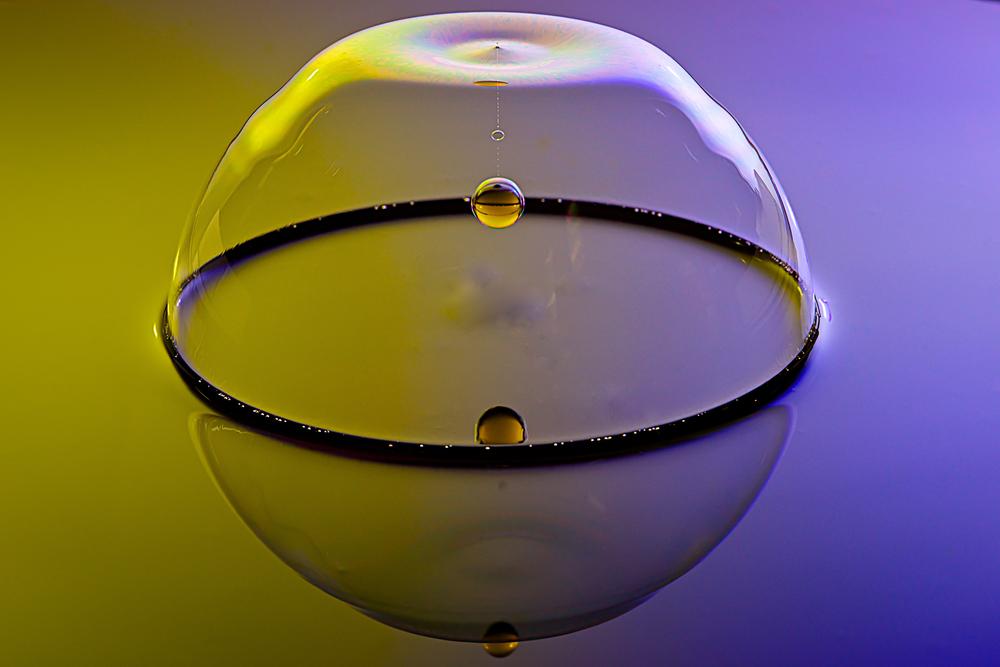 Druppel doorboort zeepbel