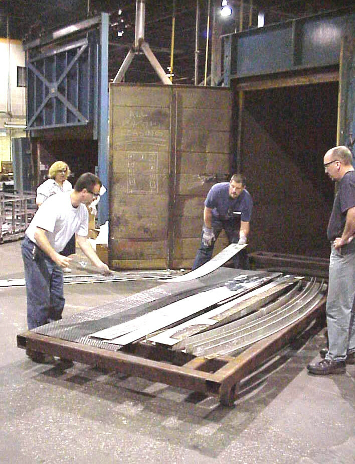 "Figure 5. ""Outer Z Ring"" components, which constitute the building's floor structure, are racked in preparation for placement in a furnace which will heat treat them for improved corrosion resistance. Photograph courtesy of the William Graham family and Henry Ford Museum & Greenfield Village."