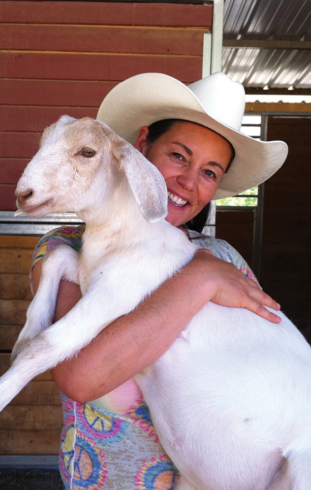 Ellie with Pixie, an orphaned goat who has found a home at the Gentle Barn.