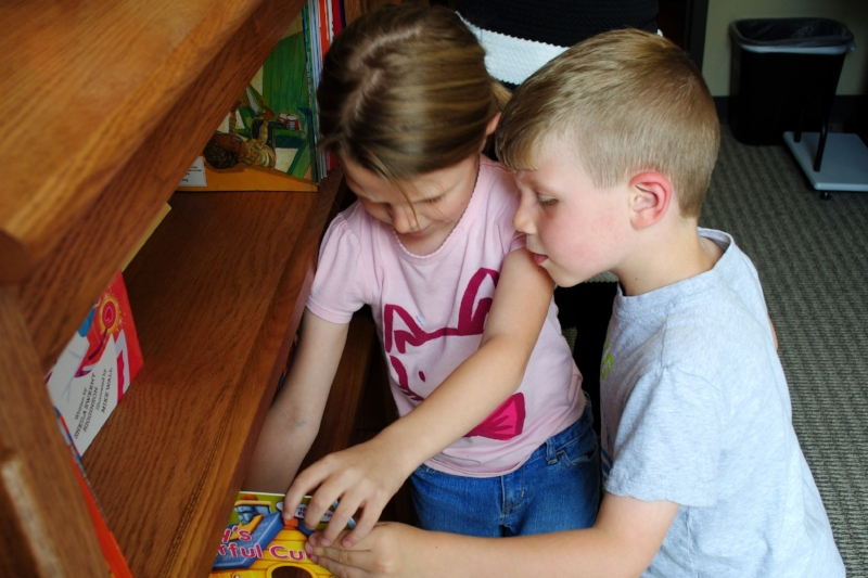 Two children check out the books in Domestic Violence Intervention Services (DVIS)'s library during the April 2016 dedication ceremony.