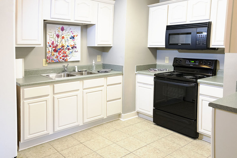 Kitchen with double sink, stove and oven, full refrigerator / freezer
