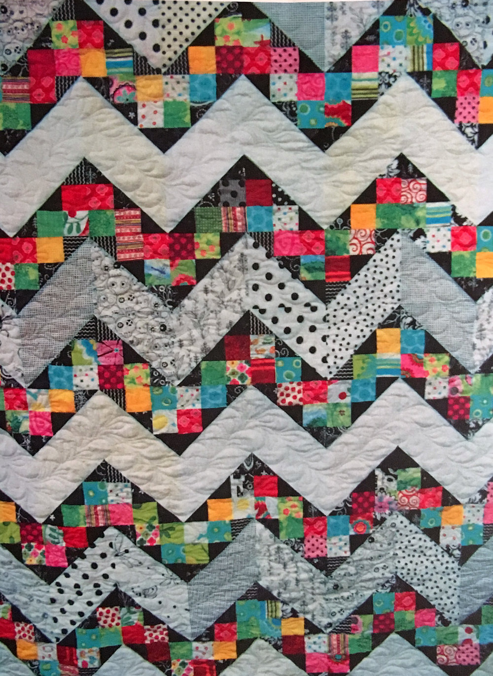 This quilt top puts a twist on the traditional chevron. You'll need 3 yards white or light colored fabric (use up those light colored prints!), 1.5 yards black or dark colored fabric, 2 yards assorted prints (for the colored blocks inside the chevron.)   $40