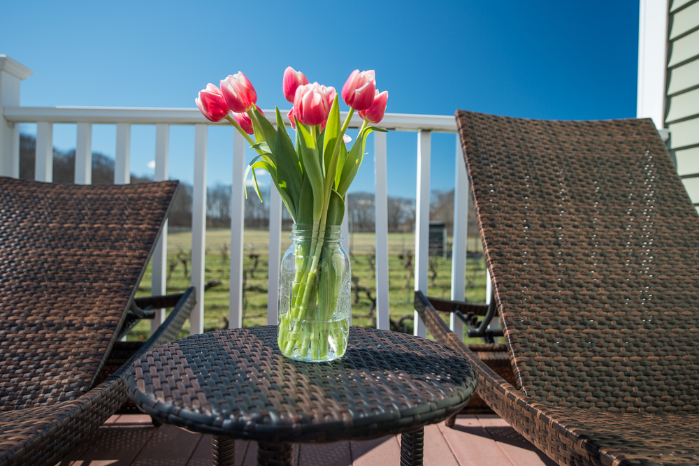 flowers on table outside with deck chairs