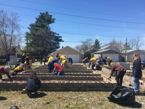 "UIndy Community Garden - The UIndy garden is located on the west side of the United Methodist Church at 4002 Otterbein Ave. On Friday, April 20, volunteers from University of Indianapolis, Community Health Network, Purdue Extension and SoIndy QOLP cleaned nine raised garden beds, glued the bed's cement blocks, shoveled and spread dirt, pulled weeds, and did some planting. ""We know that social determinants, like a lack of access to nutritious food, can affect overall health and well-being,"" said Priscilla Keith, Executive Director of Community Benefit for Community Health Network. ""We are proud to work with our partners at UIndy to offer this pilot program which will not only provide access to fresh and affordable food; but educate students and those living in neighborhoods around the UIndy campus how to start and maintain their own gardens. Our goal is to find ways to reach beyond our sites of care to impact the health and the quality of life of the communities we serve."""