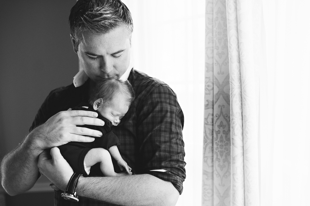 A father holding a newborn, photographed by Green and Grey Photography in Loudoun County Virginina.