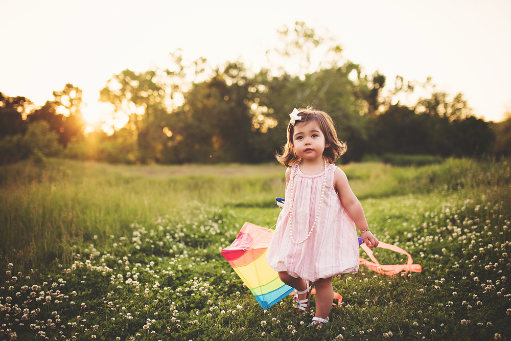 A young girl with a colorful kite, photographed in a field by Green and Grey Photography, a Northern Virginia family and child photographer.