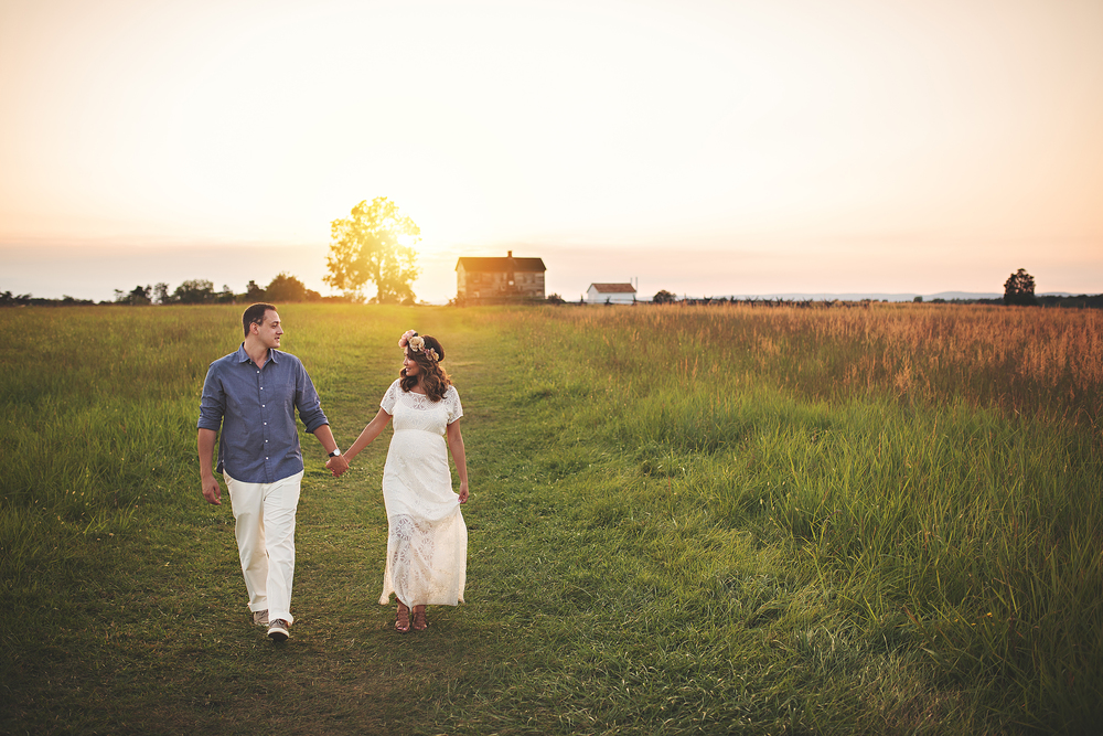 A young couple walking in a farm field with a sunset in the background.  this maternity session was photographed by Green and Grey Photography in Loudoun County Virginia.