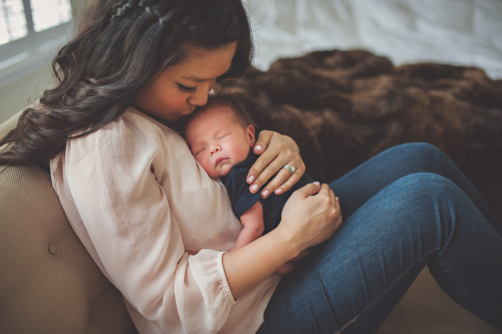 A mother and newborn embracing in this photograph by Green and Grey Photography, a Northern Virginia family photographer specializing in family and newborns.