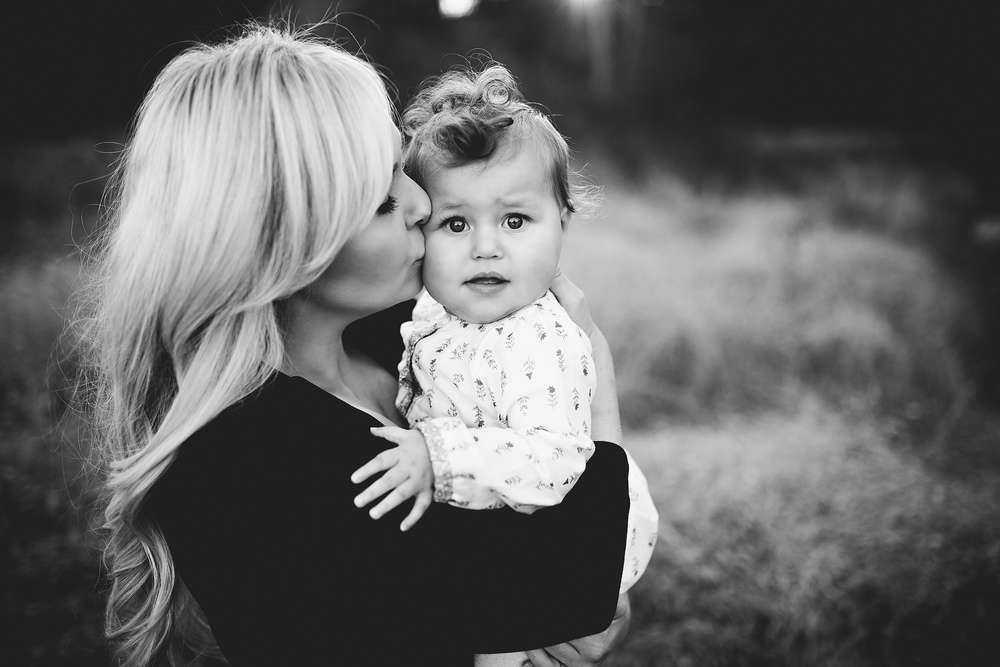 A black and white photo of a young mom kissing her baby girl.  This family photograph was taken by Green and Grey Photography, a Northern Virginina family photogrpaher.