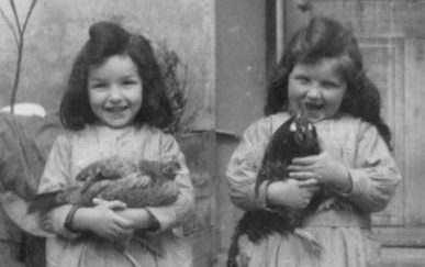 Two Jewish sisters a few years before they were sent to Auschwitz, each holding a chicken. Their dolls are being donated to a Holocaust museum in Paris