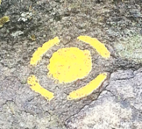 An example of a colored dot on a boulder at Font, denoting that this particular problem is a part of the yellow, or facile (easy) circuit.