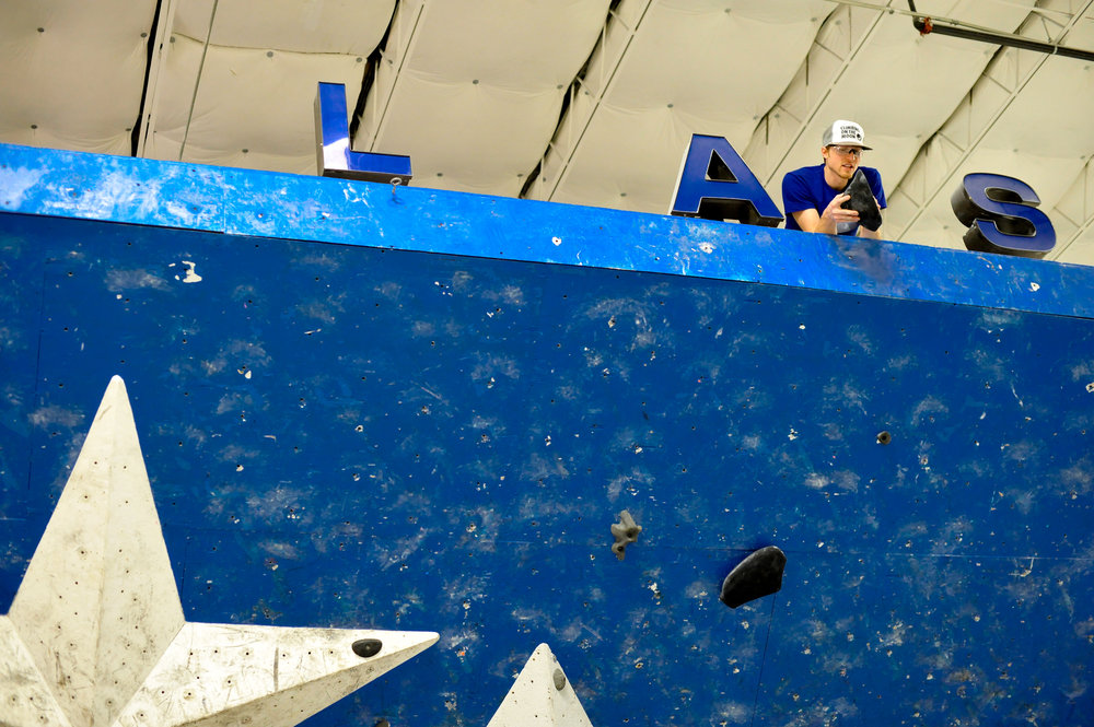 Let's play spot the routesetter! Setter Jon Correll scoping out the finish hold for a competition finals problem.