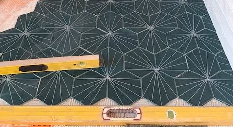 "Fireclay tile, custom 6"" hexagon with screen print used on shower floor."