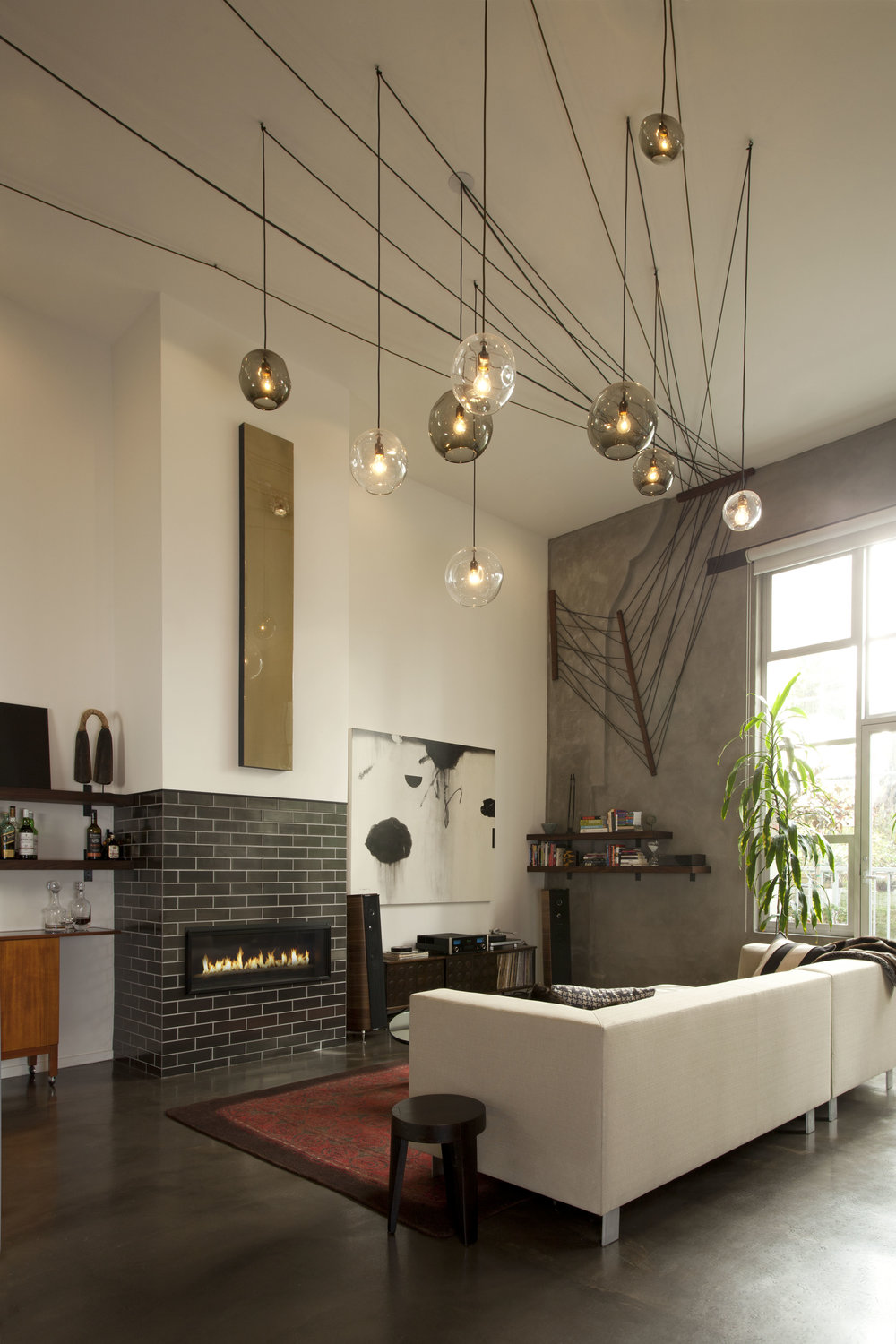 Tall ceilings warmed by custom light fixture inspired by remaining curtain pulley system.