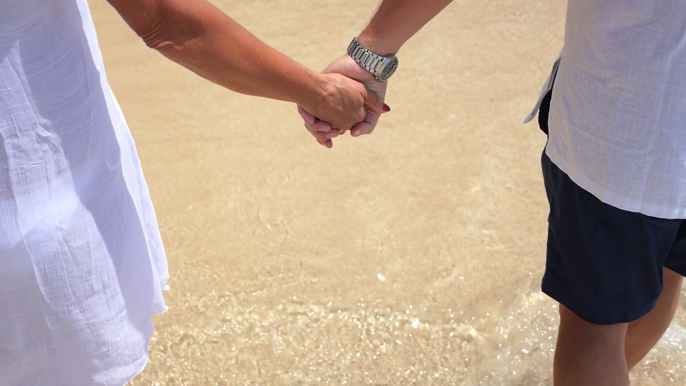 videoblocks-middle-aged-couple-holding-hands-walking-at-beach_sfz7oif3l_thumbnail-full01.png