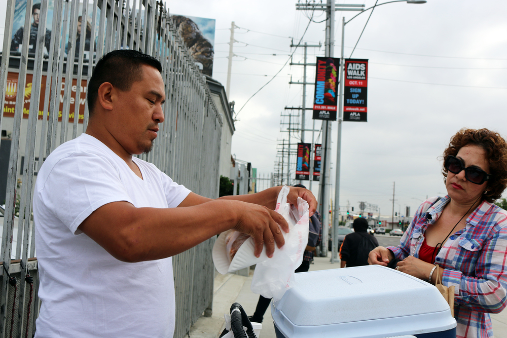 Marcos serving a tamal to a L.A. morning metro commuter