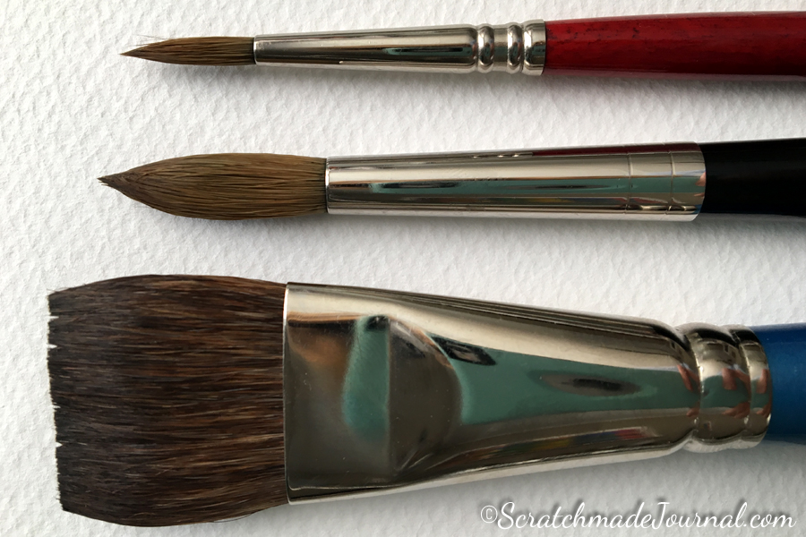 Recommended beginner watercolor brushes include (from the top) a size 6 round, a size 10 round, and a 1-inch flat.
