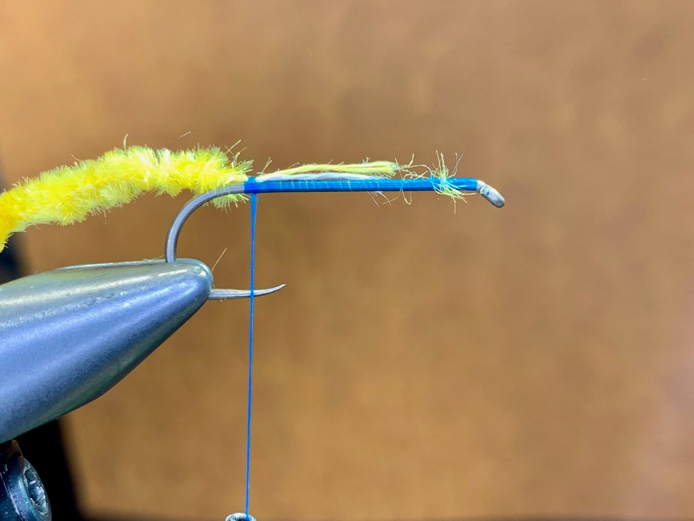 Step 2 - Prepare the chenille by stripping away the fibers, exposing the thread core. Expose a length of thread core equal to three quarters the length of the hook shank and secure to to the hook near the bend.