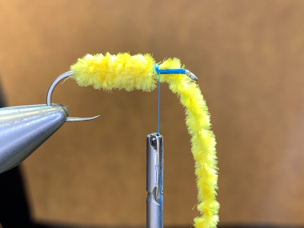 Step 4 - With close touching wraps, wind the chenille around the hook stopping 3/4 of the way up the shank. Secure the chenille with thread wraps and cut away excess.Tip: I usually leave a short tag of chenille which I then tie down along the hook shank in front of the body. This will help add bulk to the head later on in the tying process.