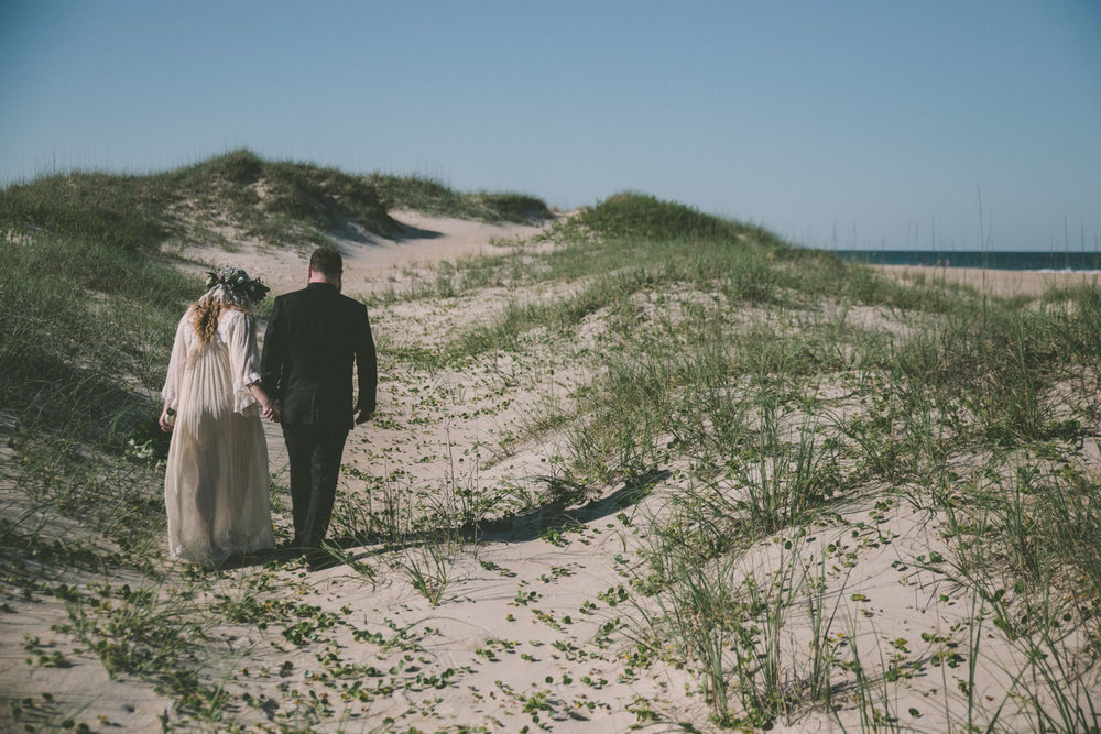 bride and groom walking on obx beach dunes.jpg