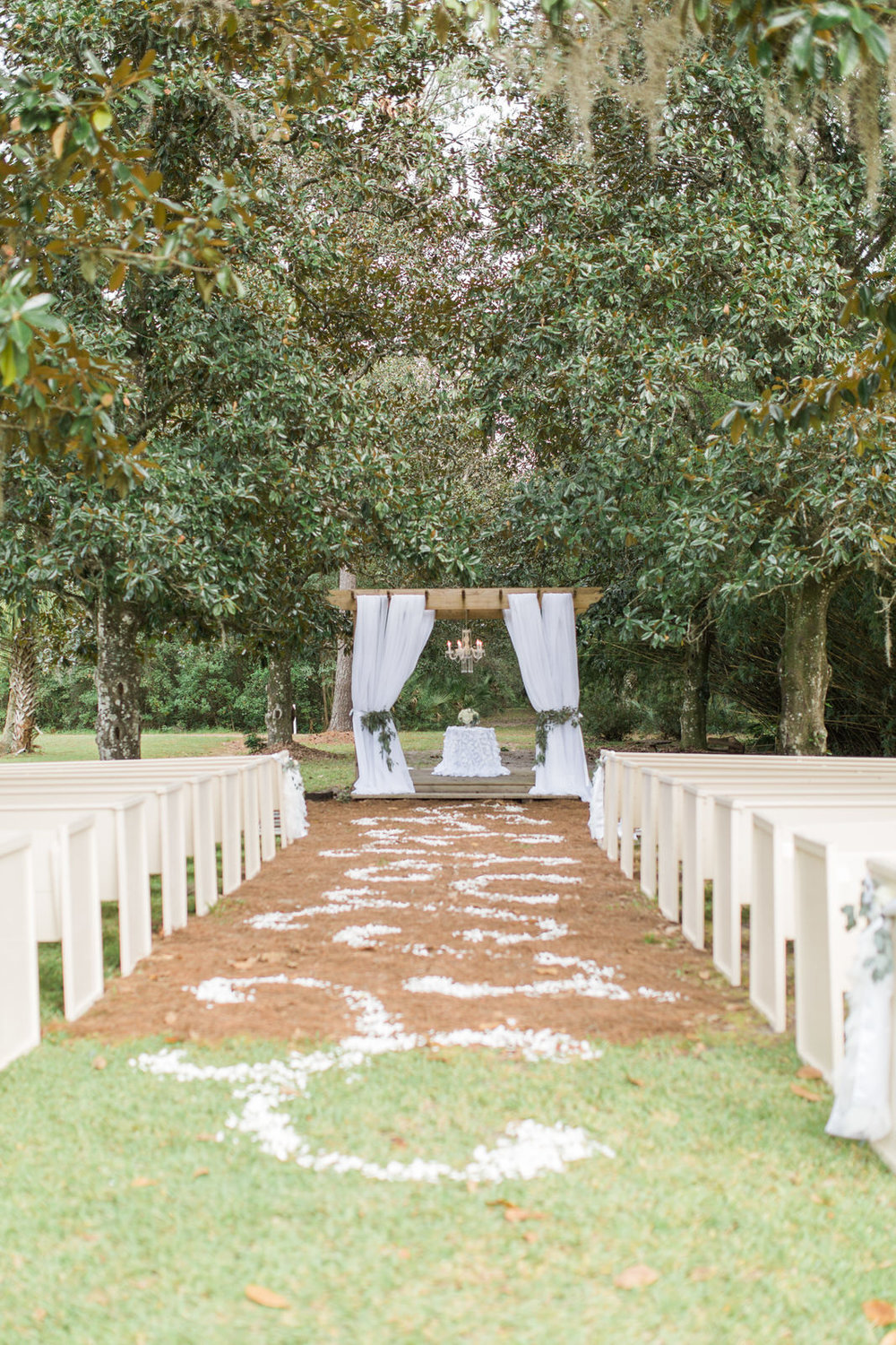 Outdoor wedding reception under trees, rose petals lining aisle, fabric draped gazebo