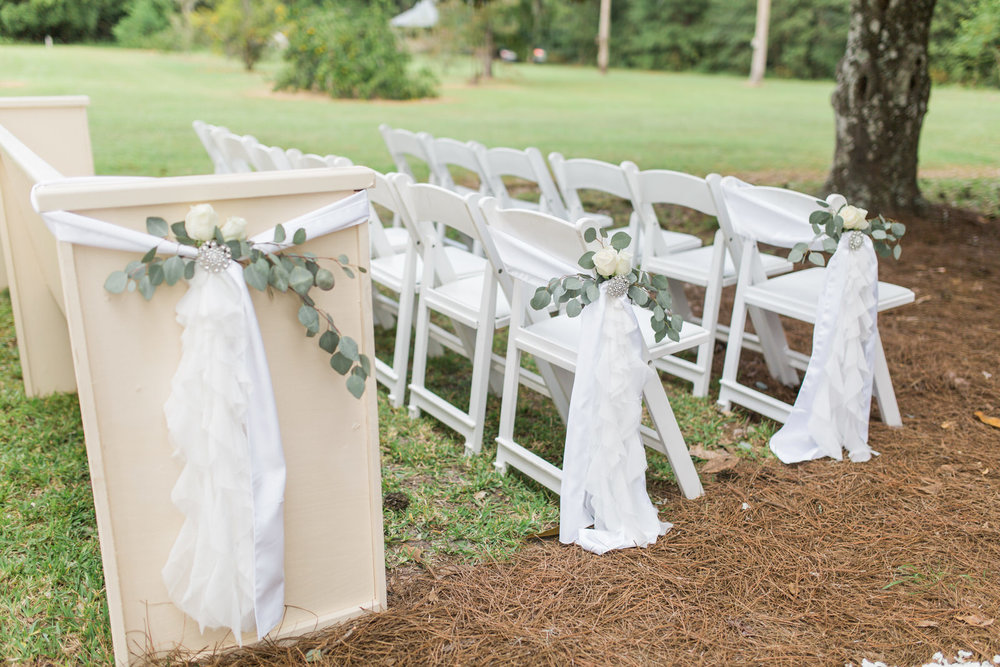 aisle decor for wedding reception including soft fabric draping and eucalyptus