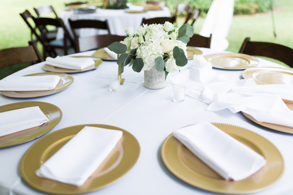 Wedding reception decor with simple white flower arrangements and gold chargers